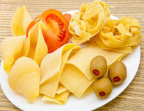 Different pasta with olives and tomat on a plate Royalty Free Stock Image