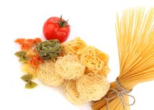 Different pasta and tomato on a white background Royalty Free Stock Images