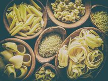 Different pasta types in wooden bowls on the table. Top view. Royalty Free Stock Image
