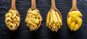 Different pasta types in wooden spoons on the table. Top view. Stock Image