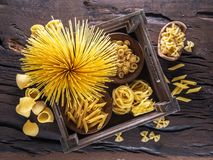 Different pasta types on the wooden table. Top view. Stock Images