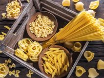 Different pasta types on the wooden table. Top view. Royalty Free Stock Image