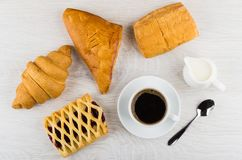 Different pastry, coffee in cup, jug of milk and spoon. Different pastry, black coffee in cup, jug of milk and spoon on wooden table. Top view Stock Images