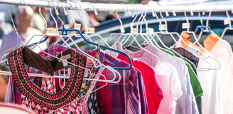 Different pattern shirts and beautiful summer women fast fashion blouses. Display on rack at garage sale to resale, reuse or exchange outdoor royalty free stock image
