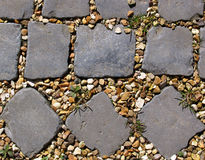 Different patterns of cobbles. The end of a nice, natural, cobbled path, showing two different cobble patterns, with golden gravel and some weeds between the royalty free stock image