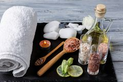 Different pebbles, bath towel and massage oil for spa procedures on a dark surface. Different pebbles of different shapes, fluffy bath towel and massage oil for Stock Photo
