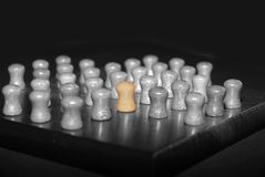 A Different peg. Black and white picture peg of a solitaire game with the central peg colored. Concept of difference, loneliness stock photos