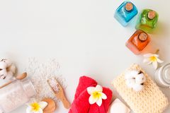 Different personal hygiene objects on white wooden background. Bath salt, lotions, pink towels and cotton flower with copy space. Different personal hygiene Royalty Free Stock Photo