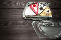 Different pieces of cake in plastic container on dark wood background stock photography