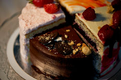 The different pieces of the cake smoothly rotate on the base. There is chocolate, carrot, yogurt and berries. Royalty Free Stock Photography