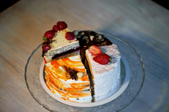 The different pieces of the cake smoothly rotate on the base. There is chocolate, carrot, yogurt and berries. Stock Photography