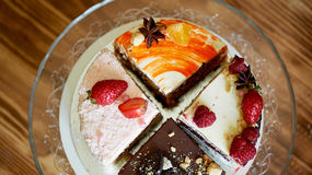The different pieces of the cake smoothly rotate on the base. There is chocolate, carrot, yogurt and berries. Stock Image