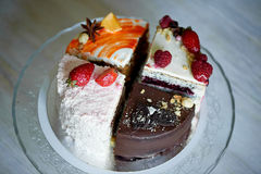 The different pieces of the cake smoothly rotate on the base. There is chocolate, carrot, yogurt and berries. Stock Images