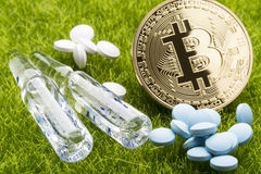 Different pills and ampules with bitcoin coin on the grass background - healthcare cost concept Royalty Free Stock Photo