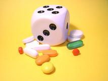 Different pills around a dice. Detail view of colored pills and capsules around a dice over a yellow background - conceptual link with missing information and Stock Photography