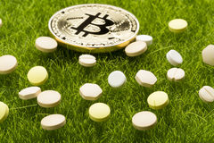 Different pills and bitcoin coin - healthcare cost concept Stock Photo