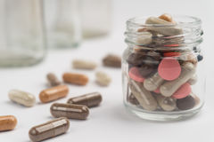 Different pills and capsules in glass jar. On white background Royalty Free Stock Photo