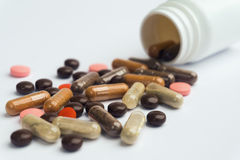 Different pills and capsules scattered on a white background. Plastic jar Royalty Free Stock Image