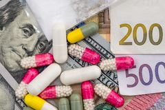 different pills on dollar and euro bills Royalty Free Stock Image