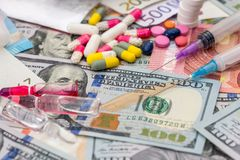 Different pills on euro and dollar bills. Royalty Free Stock Photography