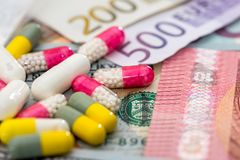 Different pills on euro and dollar bills Royalty Free Stock Image