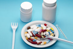 Different colorful pills on a plate with two bottle Royalty Free Stock Photos