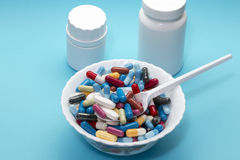 Different pills on a plate and two white bottle Royalty Free Stock Photography