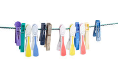 Different plastic and wooden clothespins on the clothes line. Several different spring-type new and old varicolored plastic clothespins and one old wooden Royalty Free Stock Photos