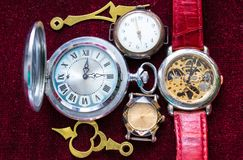 Different watches and hands are on the red velvet. Different pocket and wrist watches and hands are on red velvet royalty free stock images