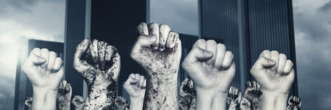 Different raising up left fists in front of skyscraper. And grey clouds Royalty Free Stock Images