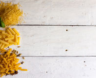 Different raw sorts of pasta and basil Royalty Free Stock Photo