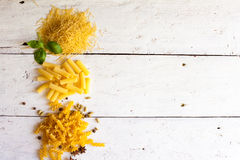 Different raw sorts of pasta and basil Royalty Free Stock Photos
