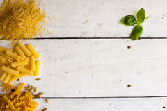 Different raw sorts of pasta and basil Stock Photos