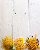 Different raw sorts of pasta and basil Royalty Free Stock Image