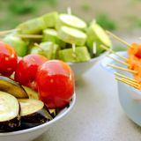 Different raw vegetables, strung on a skewer for grilling. Prepa. Red for a picnic. Concept of healthy, useful food. Selective focus. Square. Close-up Stock Photos