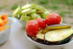 Different raw vegetables, strung on a skewer for grilling. Prepa. Red for a picnic. Concept of healthy, useful food. Selective focus. Close-up Royalty Free Stock Images