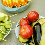 Different raw vegetables, strung on a skewer for grilling. Prepa. Red for a picnic. Concept of healthy, useful food. Selective focus. Square. Close-up Royalty Free Stock Image