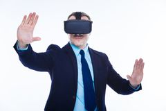 Smart confident businessman experiencing 3d reality. Different reality. Smart nice confident man wearing 3d glasses and moving his hands while experiencing 3d Royalty Free Stock Photos