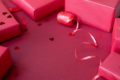 Different red boxes, ribbon and confetti on red background. Concept for Valentine's Day stock photo