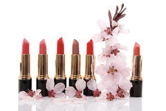 Different red lipstick and cherry flower Royalty Free Stock Image