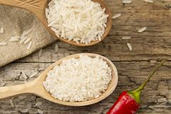 Different rice in spoons on wooden background. Healthy eating, diet Royalty Free Stock Photo
