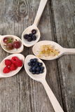 Different ripe berries in a wooden spoons Royalty Free Stock Photo