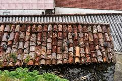 Different roof coverings on older buildings. View of the roofs of older buildings, each roof has a different color and type of roofing, tile, corrugated iron royalty free stock photography