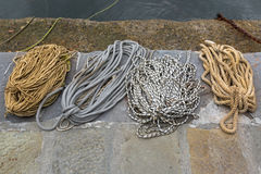 Different ropes to tie boats, old rusty chains used in fishing i Royalty Free Stock Images
