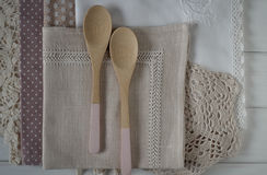 Different rustic linen napkin. And wooden spoons top view on white background Stock Image
