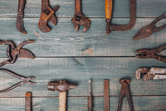 Different rusty construction instruments on the green wooden background Stock Image