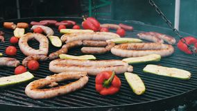 Different sausages are roasted on huge grill with vegetables. Food Festival stock video footage