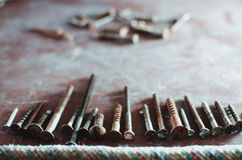 Different screws and bolts. On the old table are the screws in different sizes and nails, texture background Stock Image