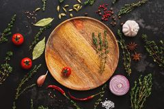 Different seasoning for cooking on a dark background. Empty wooden plate, spices, herbs, vegetables. Top view, flat lay