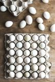 Different shade of color farm fresh eggs in carton on wood stock photo